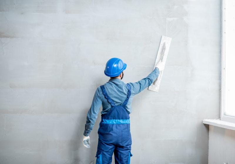 man plastering an interior wall