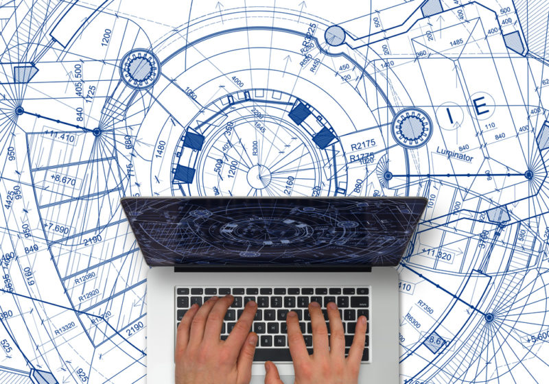 computer with hands on top of blueprints